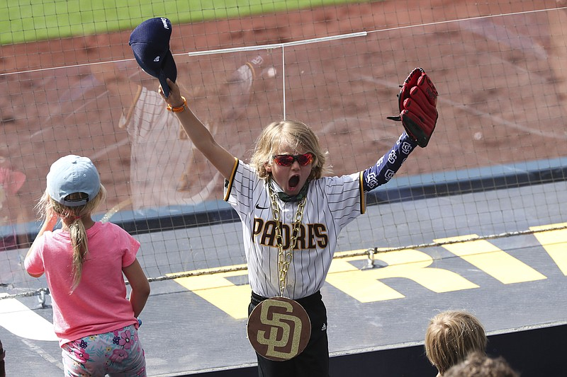A young San Diego Padres fan cheers for the team during a baseball game again...