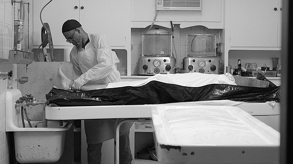 Funeral worker Hanif Muhammad prepares a body he's receiv...