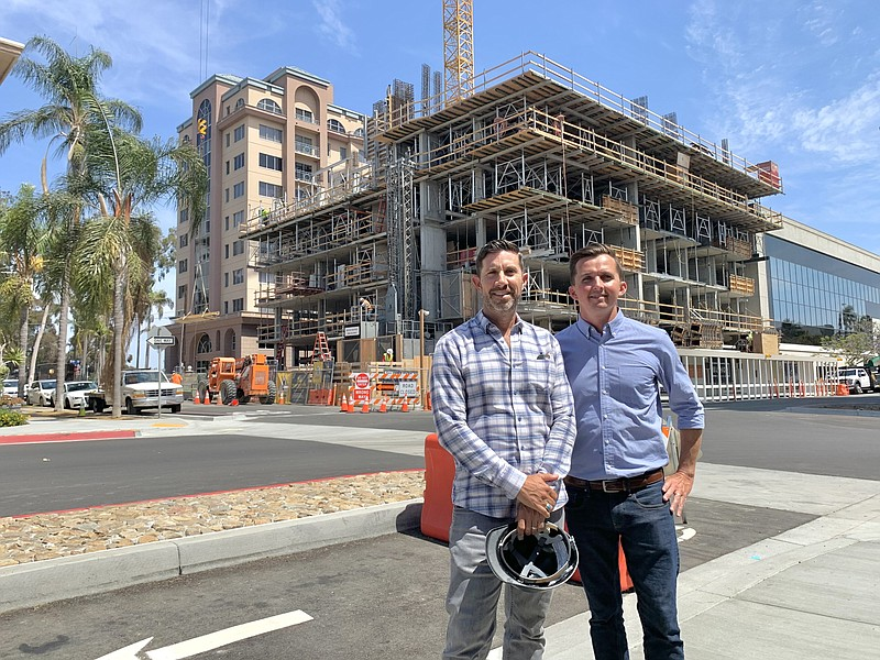 Gilman Bishop, left, and Ryan Wynn stand in front of their 100-unit apartment...