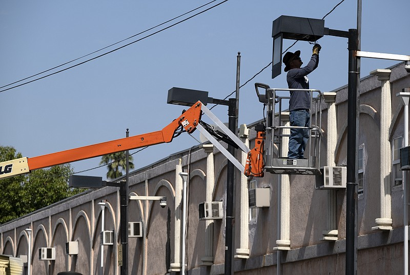 A worker fixes a street lamp in the Van Nuys section of Los Angeles on Thursd...