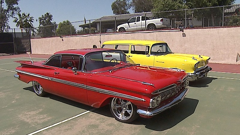 Pictured, a red 1959 Chevy Impala and a yellow 1957 Chevy Handyman Wagon park...