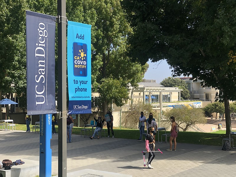 Students and faculty walk on a pathway at the UC San Diego campus, September ...