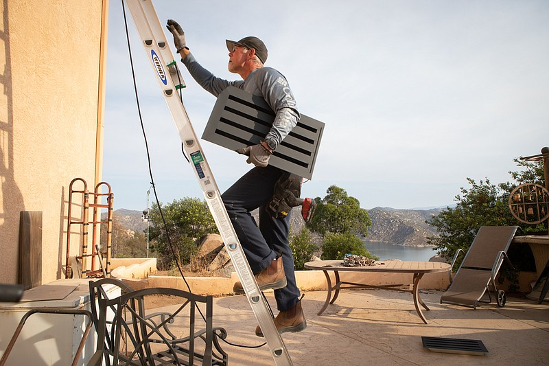 Bill Bozarth climbs a ladder to install an ember-resistant vent at a Lakeside...