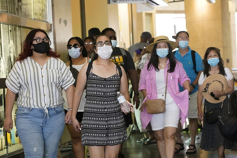 In this July 1, 2021, file photo visitors wear masks as they walk in a shoppi...