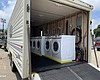 A trailer with washers and dryers inside being ...
