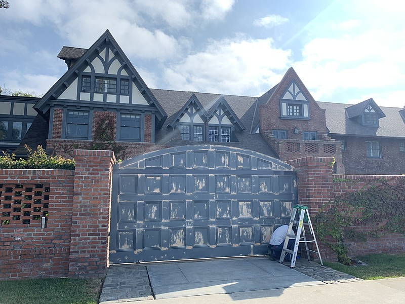 A worker prepares to repaint the front gate of a multi-million dollar beachfr...