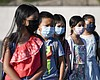 Masked students wait to be taken to their class...