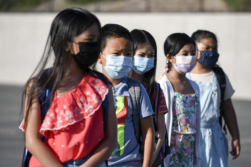 Masked students wait to be taken to their classrooms at Enrique S. Camarena E...