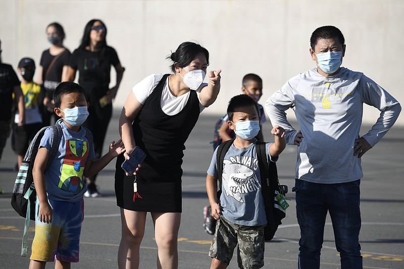 Masked parents direct their children on the first day of school at Enrique S....