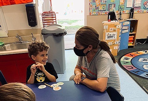 Holly Weber talks to a student at Magic Hours Preschool i...