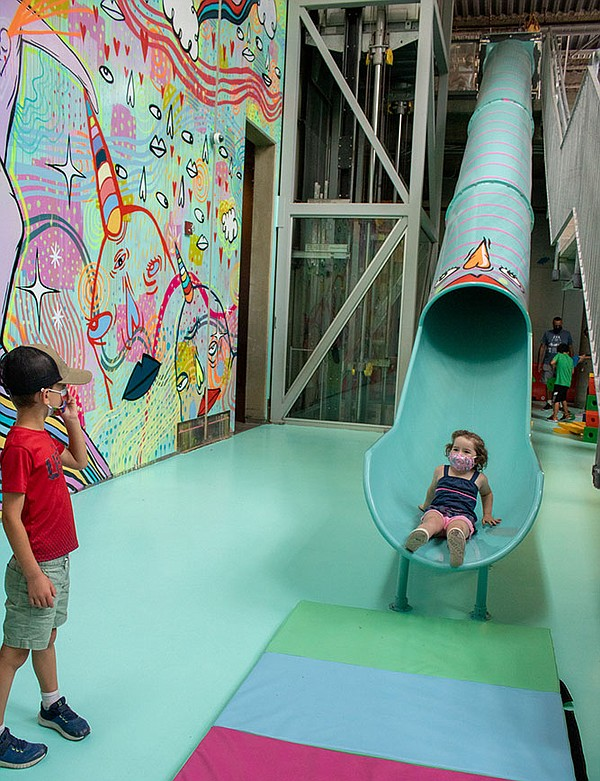 Children play on the 40-foot slide at the entrance to Pan...