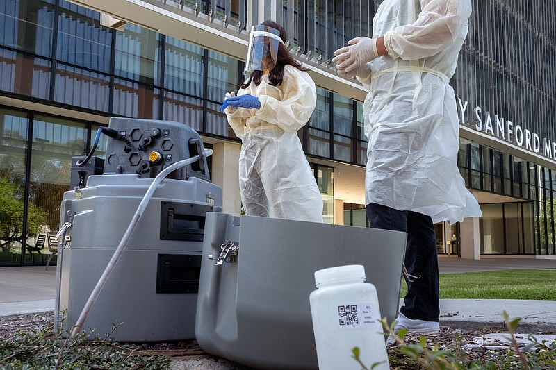 Researchers collecting data from an automated collection machine on the UC Sa...