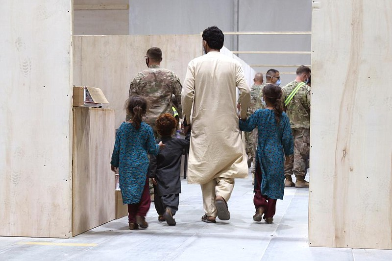 An Afghan family walks toward a medical screening station while in-processing...