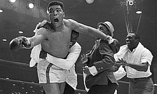 Cassius Clay's handlers hold him back after he ...