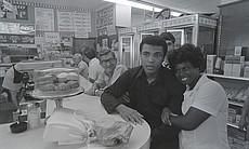 Muhammad Ali seated at a lunch counter, takes p...