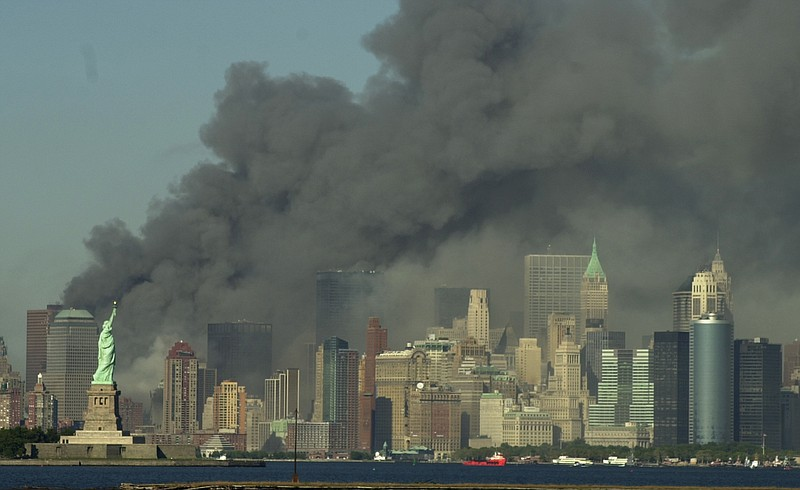 Thick smoke billows into the sky from the area behind the Statue of Liberty, ...