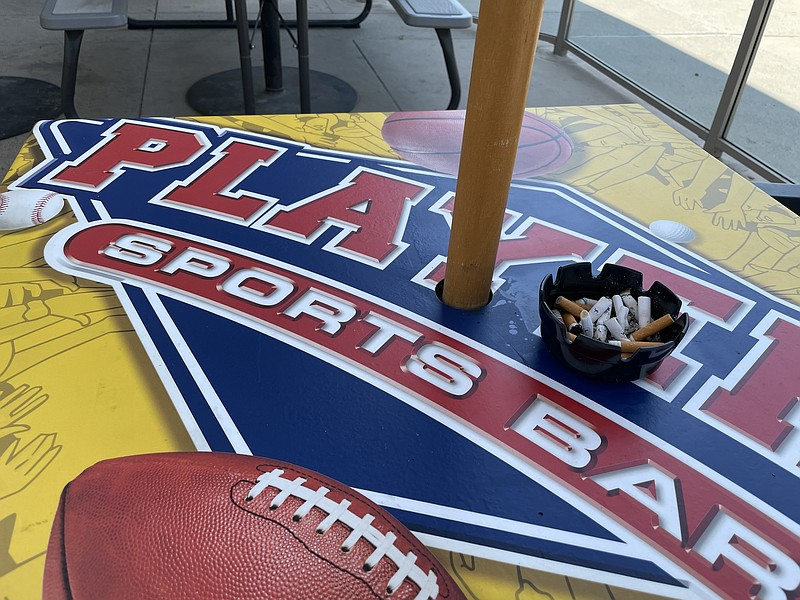 An ashtray full of cigarette butts sits on a table at Players Sports Grill's ...