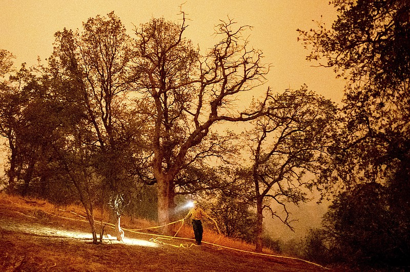 A firefighter lays hose around the Foothills Visitor Center while battling th...