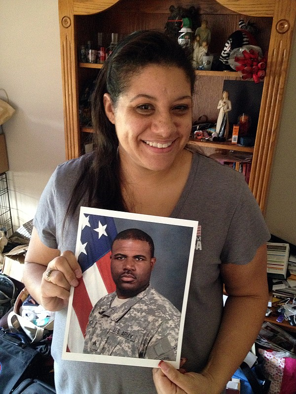 Alicia McCoy holds a photo of her husband, Sgt. Brandon M...