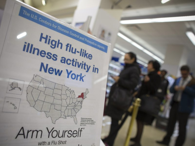 People line up at a Duane Reade pharmacy in New York behind a sign announcing...