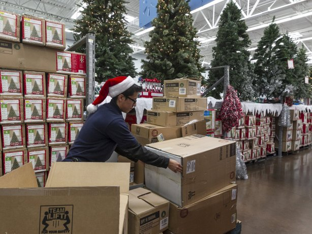 Walmart associate Angel Campos stocks Christmas decorations ahead of a pre-Black Friday event at the Walmart Supercenter store in Rosemead, California, Nov. 22, 2012.