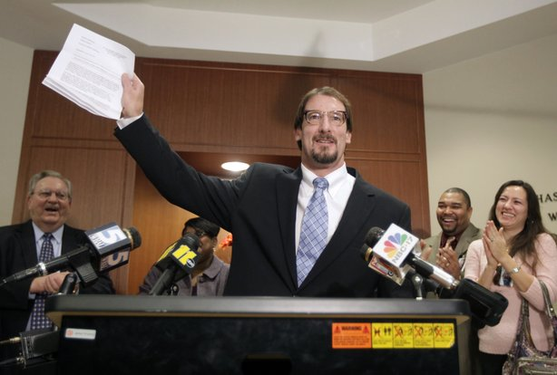 Greg Taylor holds up his release papers after he was unanimously exonerated by a three judge panel, on Feb. 17, 2010, in Raleigh, N.C. Taylor had been in prison since 1993 for murder. Taylor is now suing several people who worked at a crime lab, whose erroneous findings landed him in jail.