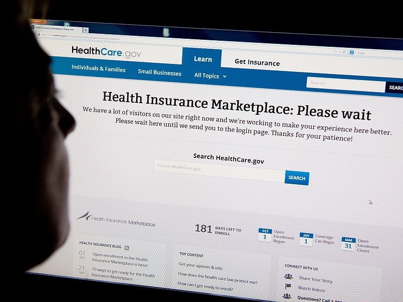 A woman looks at the HealthCare.gov insurance exchange internet site October ...