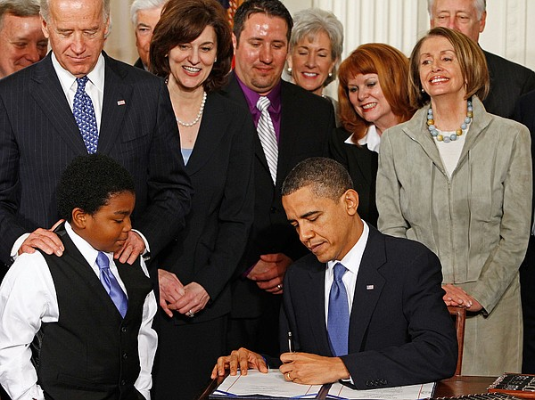 President Obama signs the Affordable Care Act at the White House on March 23,...