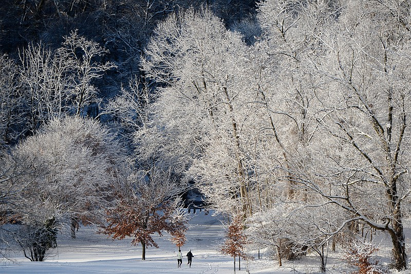 Joggers run through snow-covered Rock Creek Park, in Washington DC.