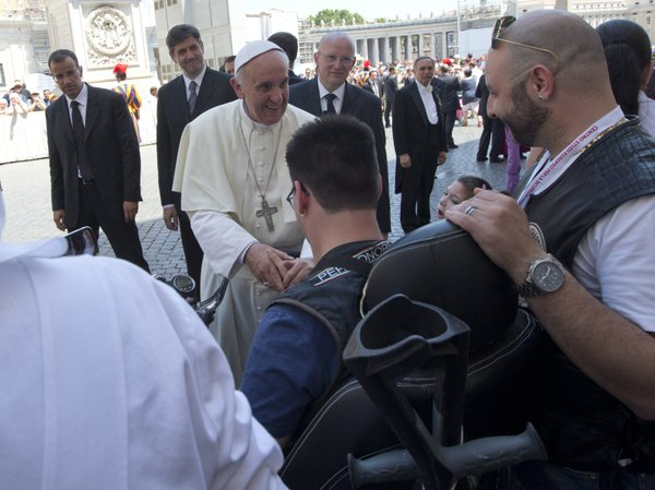 Pope Francis blesses a sick or disabled person wearing Harley-Davidson garb a...