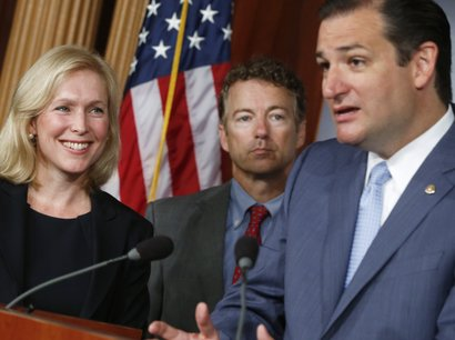 Sen. Kirsten Gillibrand, D-N.Y., left, smiles as she listens to Sen. Ted Cruz...
