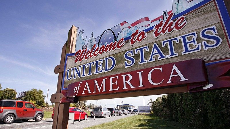 Cars entering the U.S. pass a welcome sign at the border crossing between the...