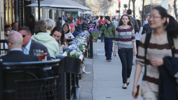 People walk and eat along Boylston Street, near the site of the Boston Marathon bombings, Wednesday. Businesses in the area have reported strong customer support; they also have an option for federal loans to help them cope with losses.