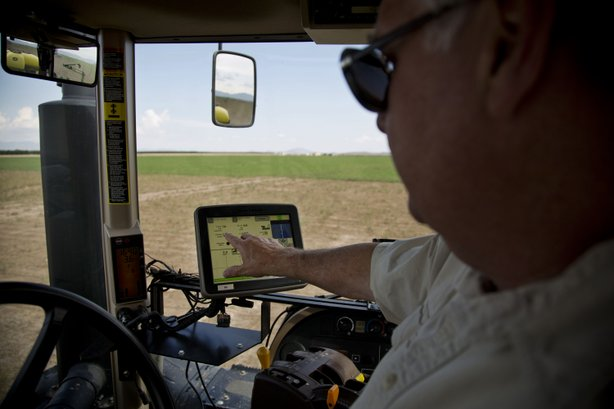Buffett rides in a tractor to show how crops are planted using GPS technology.