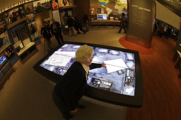 Docent Patricia Flynn demonstrates an interactive with information about conflicts in Afghanistan and Iraq.