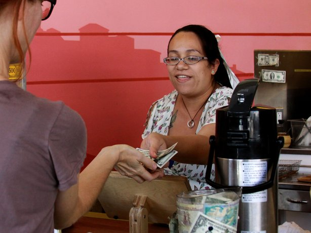 Carmen Castillo, an employee of Café de Leche, gives change back to a customer.