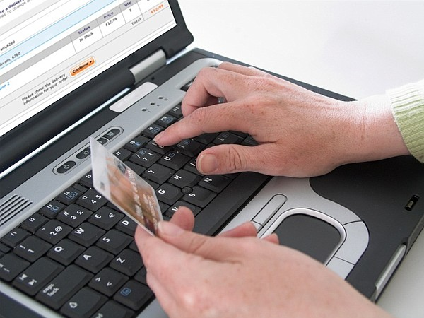 A man types credit card information into a laptop compute...