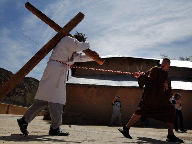 Students playing the roles of Roman soldiers lead a man playing the role of Jesus  during a reenactment of the Stations of the Cross at the Sanctuary of Chimayo in New Mexico on Thursday.