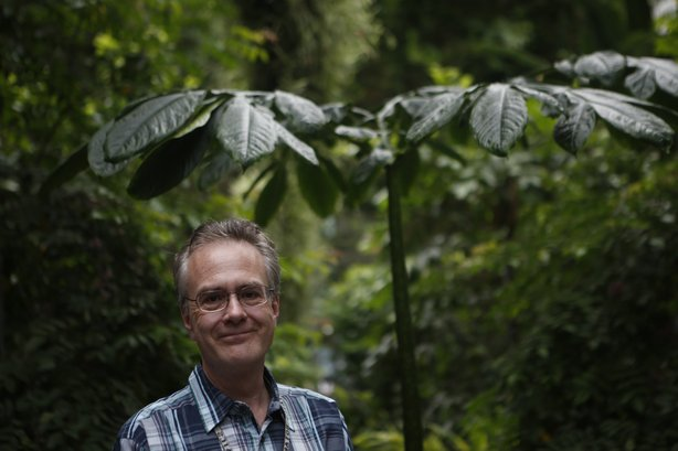 Kyle Wallach, a botanist with the U.S. Botanic Garden, stands by a non-blooming corpse flower.