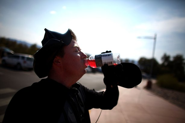 """Jonathan Rice, dressed as Darth Vader, gulps down a bottle of Vitamin Water after running a 6:36 mile in the hottest stretch of Death Valley. Rice has been doing the run to try and set a world record for the fastest mile run in a record-setting temperature and has dubbed it the """"Darth Valley Challenge."""""""