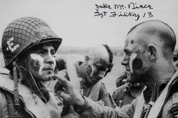 On June 5, 1944, Jake McNiece (right) led a group of paratroopers in World War II. After he shaved his head and painted his face before dropping behind German lines for D-Day, the look caught on with his men.