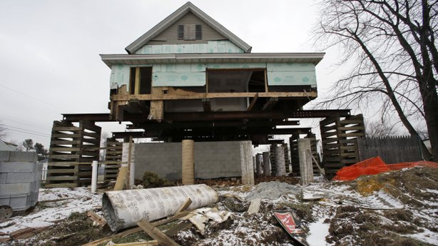 A small home damaged by Superstorm Sandy is braced in the air Tuesday, Feb. 5, 2013, in Union Beach, N.J., as workers raise it to prevent future flooding.