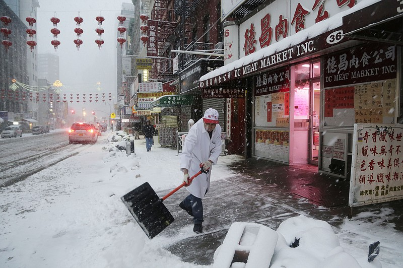 A man clears snow in front of the DC Meat Market in the Chinatown neighborhood of New York City on Thursday. Snow and sleet are falling on the East Coast, from North Carolina to New England, a day after sleet, snow and ice bombarded the Southeast.