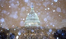 Snow falls in front of the U.S. Capitol building. The federal government's offices are closed today and more than 4,400 flights into or out of the U.S. have been canceled.