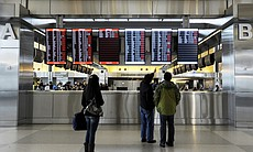 Travelers at Raleigh-Durham International Airport check on canceled departures, displayed in red, on Wednesday in Morrisville, N.C. Over 100 flights were canceled by 2 p.m. because of the winter storm hitting the area.