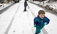 Milo Kortemeier (right) runs away from John Staton after pelting him with a snowball in Decatur, Ga. Icy road conditions caused some businesses and schools to shut down in the greater metro Atlanta region.