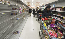 Shoppers wait beside mostly-empty shelves in a grocery store, as people stocked up on items ahead of the approaching snowstorm, in Alexandria, Va.